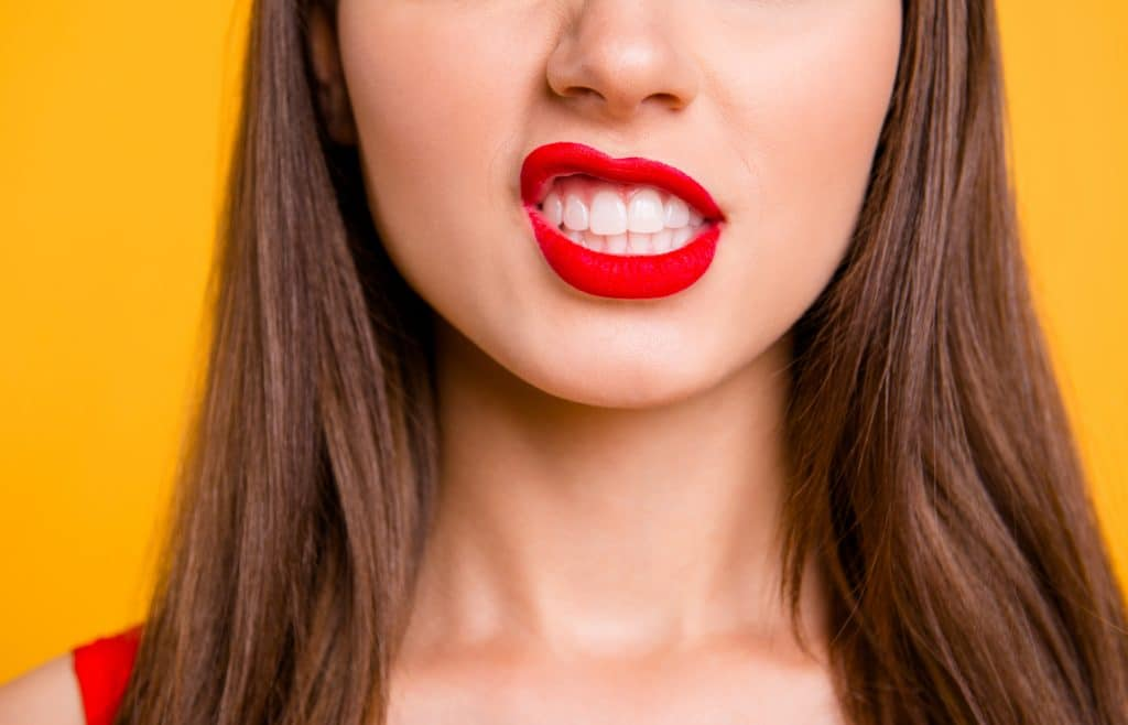 Close up cropped photo of big full natural lips brunette hair isolated on vivid yellow background