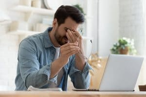 Tired young man feel pain eyestrain holding glasses rubbing dry irritated eyes fatigued from computer work, stressed man suffer from headache bad vision sight problem sit at home table using laptop