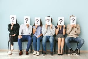 Young people hiding faces behind paper sheets with question marks while waiting for job interview indoors