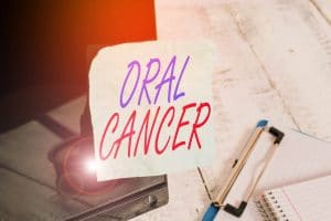 Conceptual hand writing showing Oral Cancer. Concept meaning the cancer of the lining of the lips mouth or upper throat Note paper taped to black screen near keyboard stationary