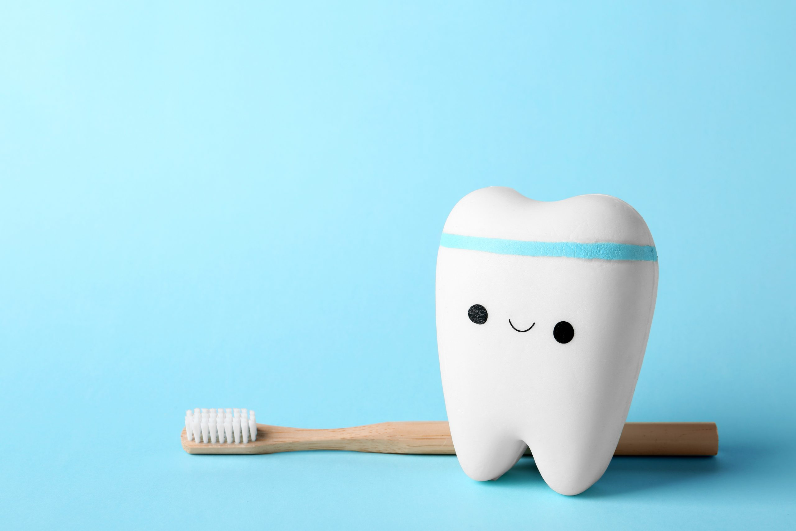 Model of tooth with happy face, brush and space for text on color background