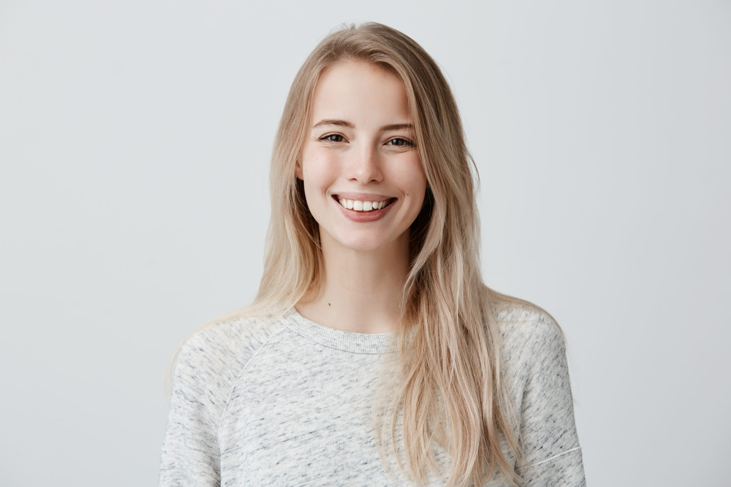 Human face expressions and emotions. Positive joyful young beautiful female with fair straight hair in casual clothing, laughing at joke, looking at camera and pleasantly smiling.