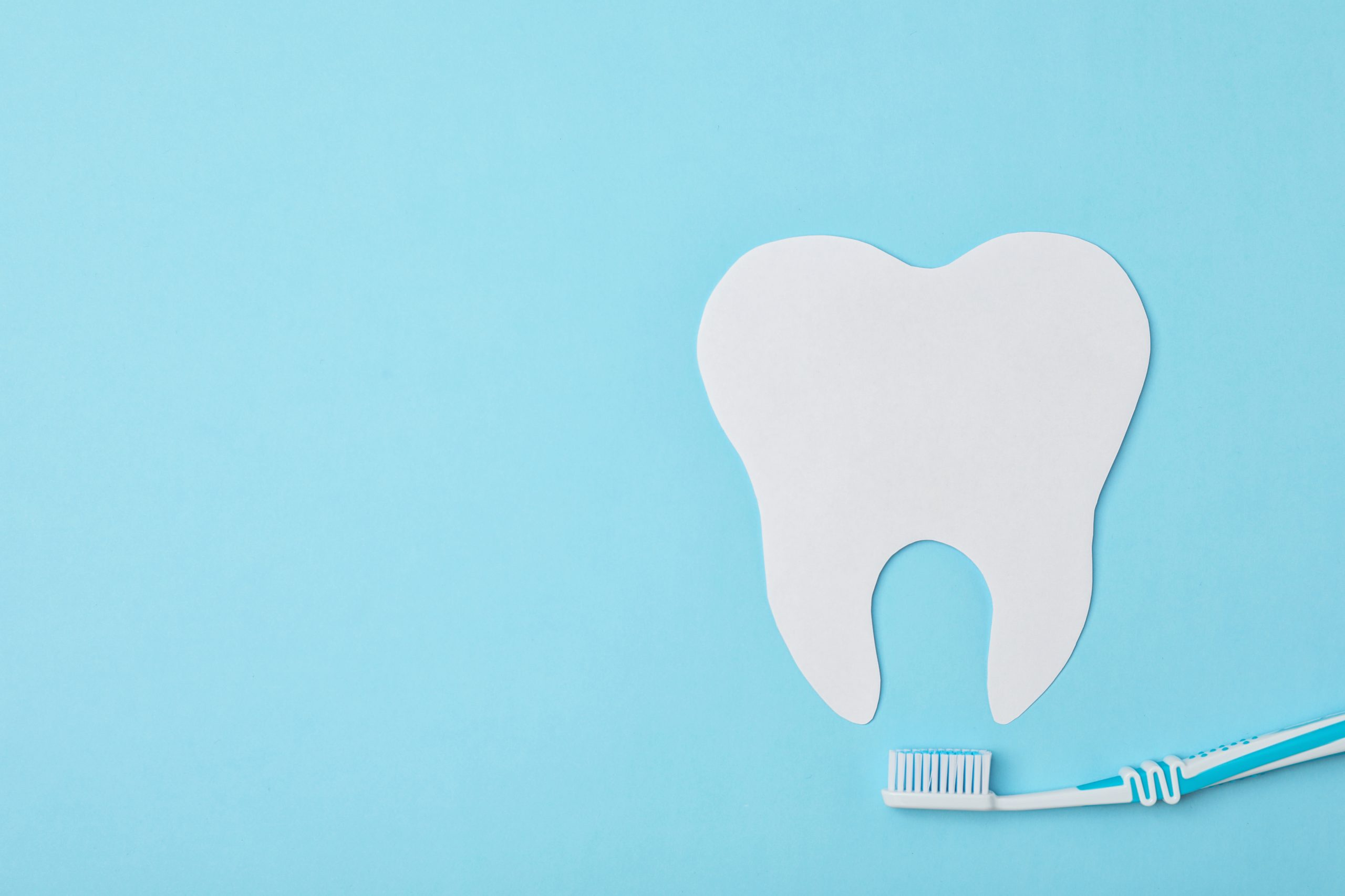Paper tooth cutout and brush on color background, flat lay with space for text. Professional dentist