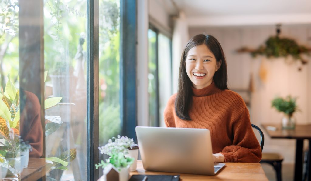 Happy young Asian girl working at a coffee shop with a laptop