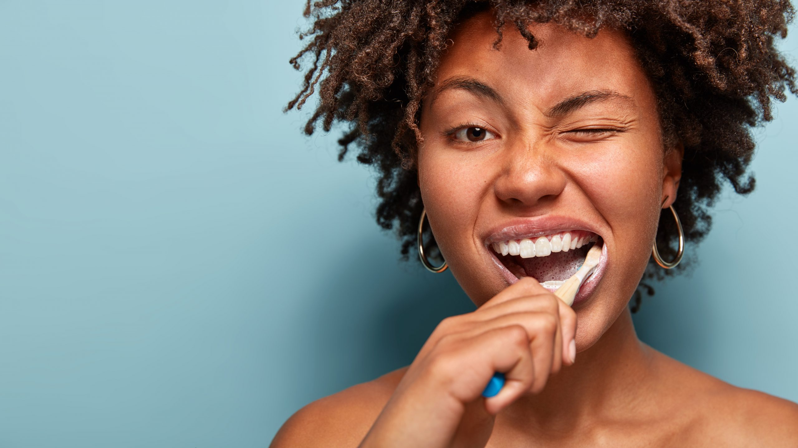 Tooth care concept. Slim naked young woman blinks eye, has daily routine after shower, brushes teeth with tootbrush, has healthy skin, isolated over blue background, free space for your promotion.