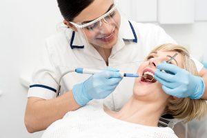 Smiling female dentist procedure of teeth cleaning