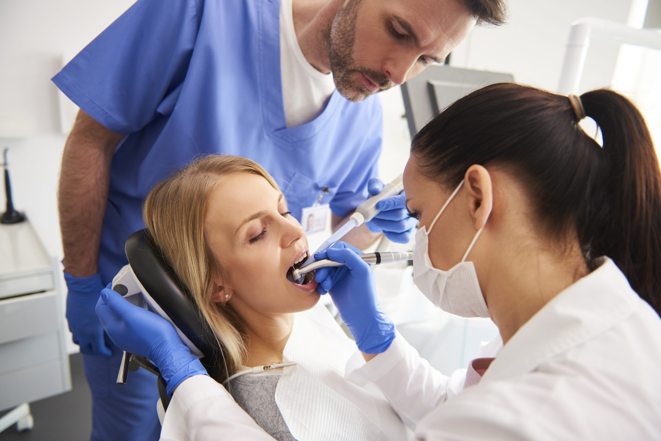 Young woman is getting treatment in dentist's office