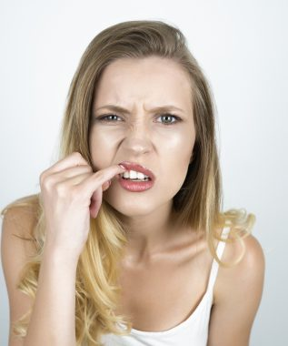 blond young woman showing her teeth with finger close up isolated white background.