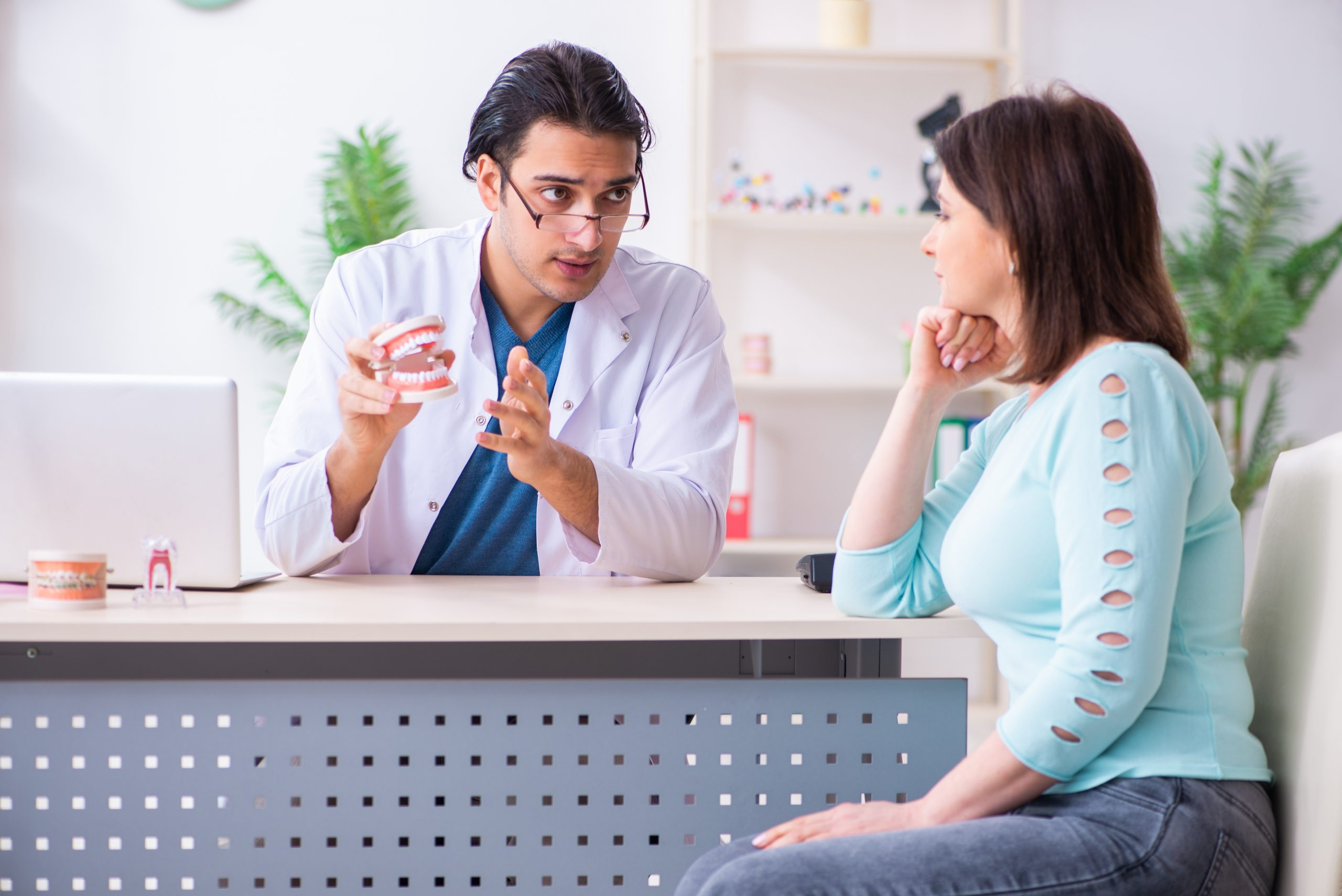 The middle-aged woman visiting male doctor stomatologist