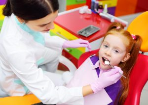 children's dentist examines the teeth and mouth of the child - a cute red-haired girl sitting in a dental chair. Pediatric dentistry
