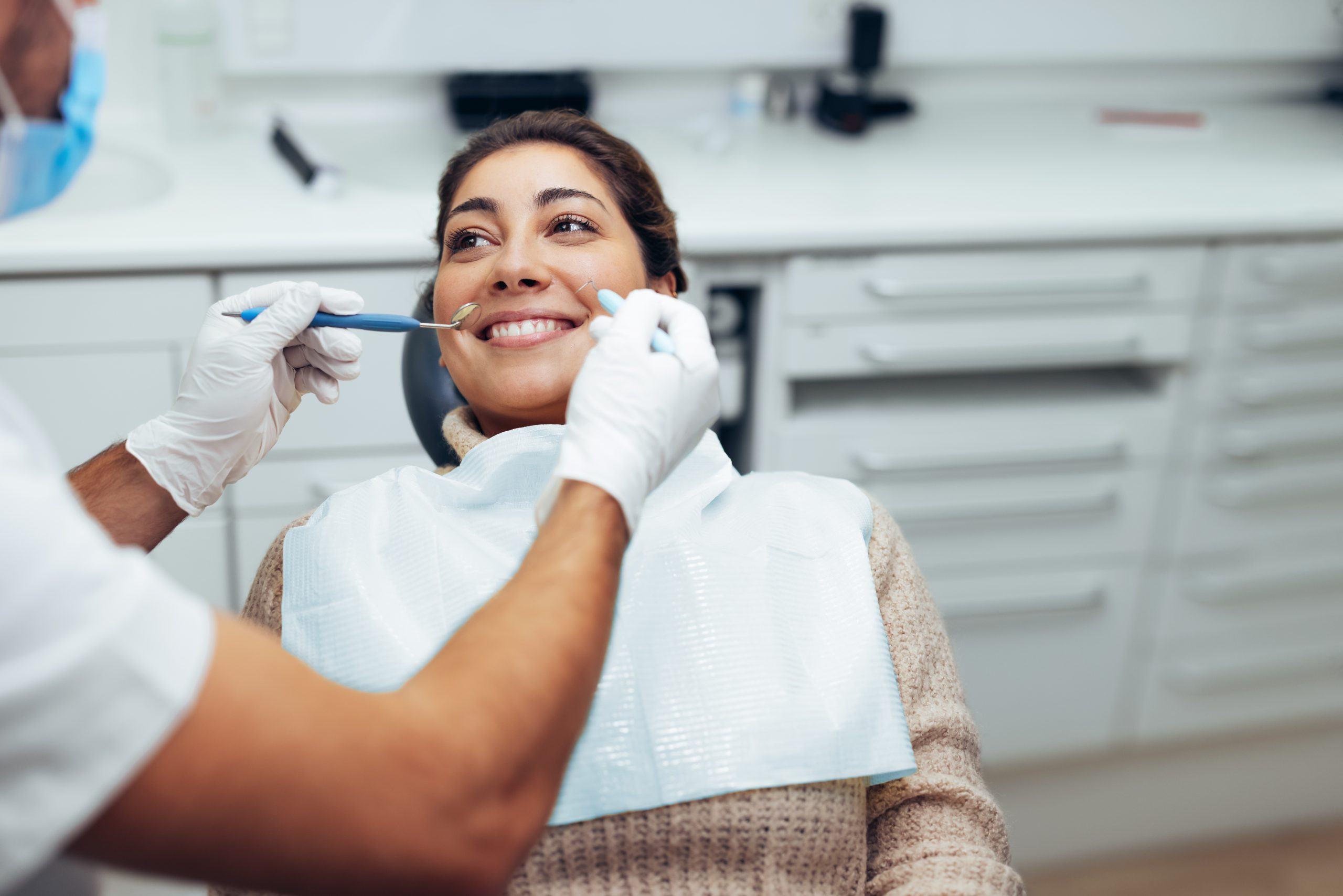 Woman getting a dental treatment at dentistry. Dentist examining the teeth of female patient with tools in clinic.