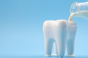 Oral health, cavity prevention and calcium rich drink for strong teeth concept with glass bottle pouring milk into a heathy tooth isolated on blue background with copy space
