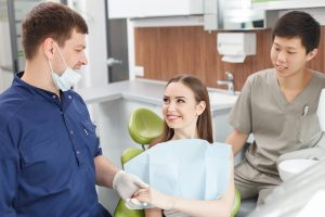 Cheerful dentist and his assistant are calming their visitor. The dentist is holding female hand with support. The woman is sitting in medical chair and looking at dentist with trust. They are smiling