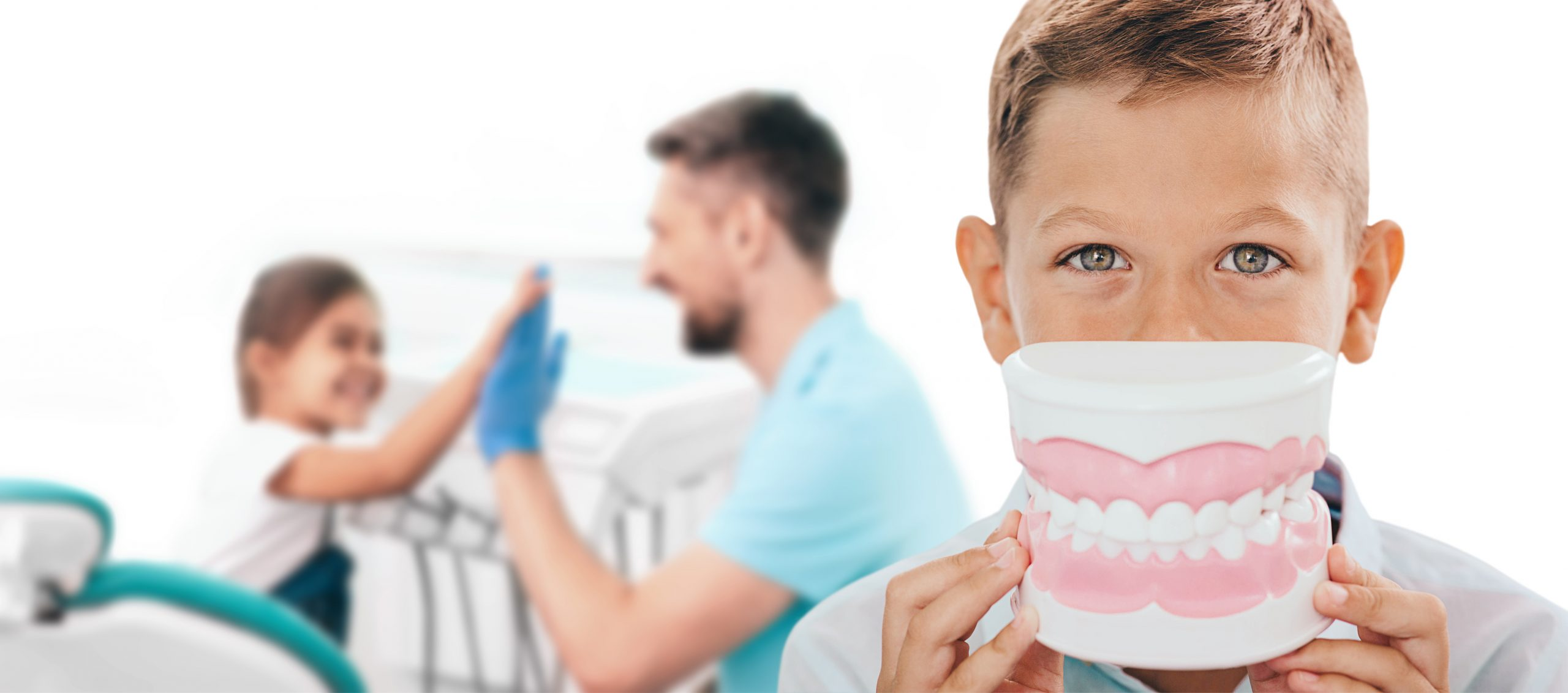 Pediatric dentistry, children teeth treatment. Boy with a large model of smile in front of the face, against the background of a dentist and a girl