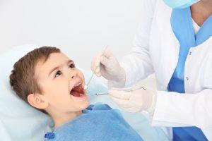 Dentist examining cute boy's teeth in modern clinic