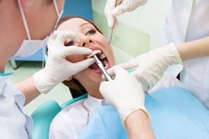 Closeup portrait dentist, his assistant carrying out thorough examination dental procedure, tooth extraction on young female patient, lying in chair, wide open mouth isolated clinic office background