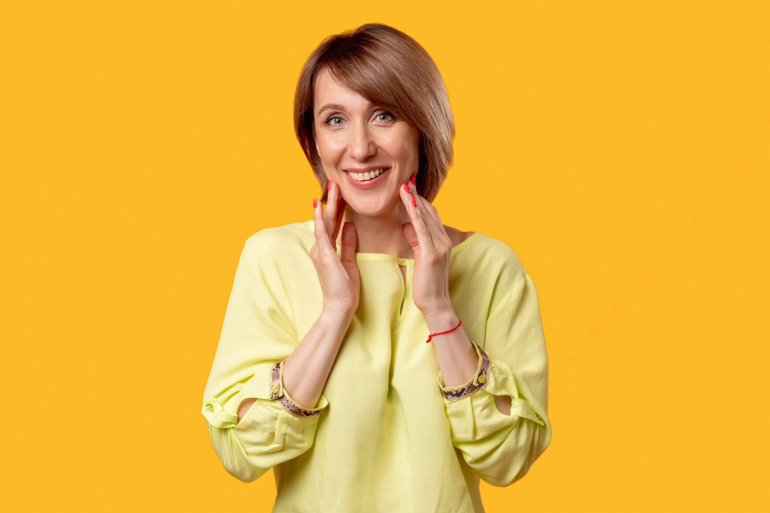 Satisfied mature woman. Face skin care. Anti-aging procedure. Aesthetic cosmetology. Portrait of positive happy lady in yellow blouse smiling isolated on orange copy space background.