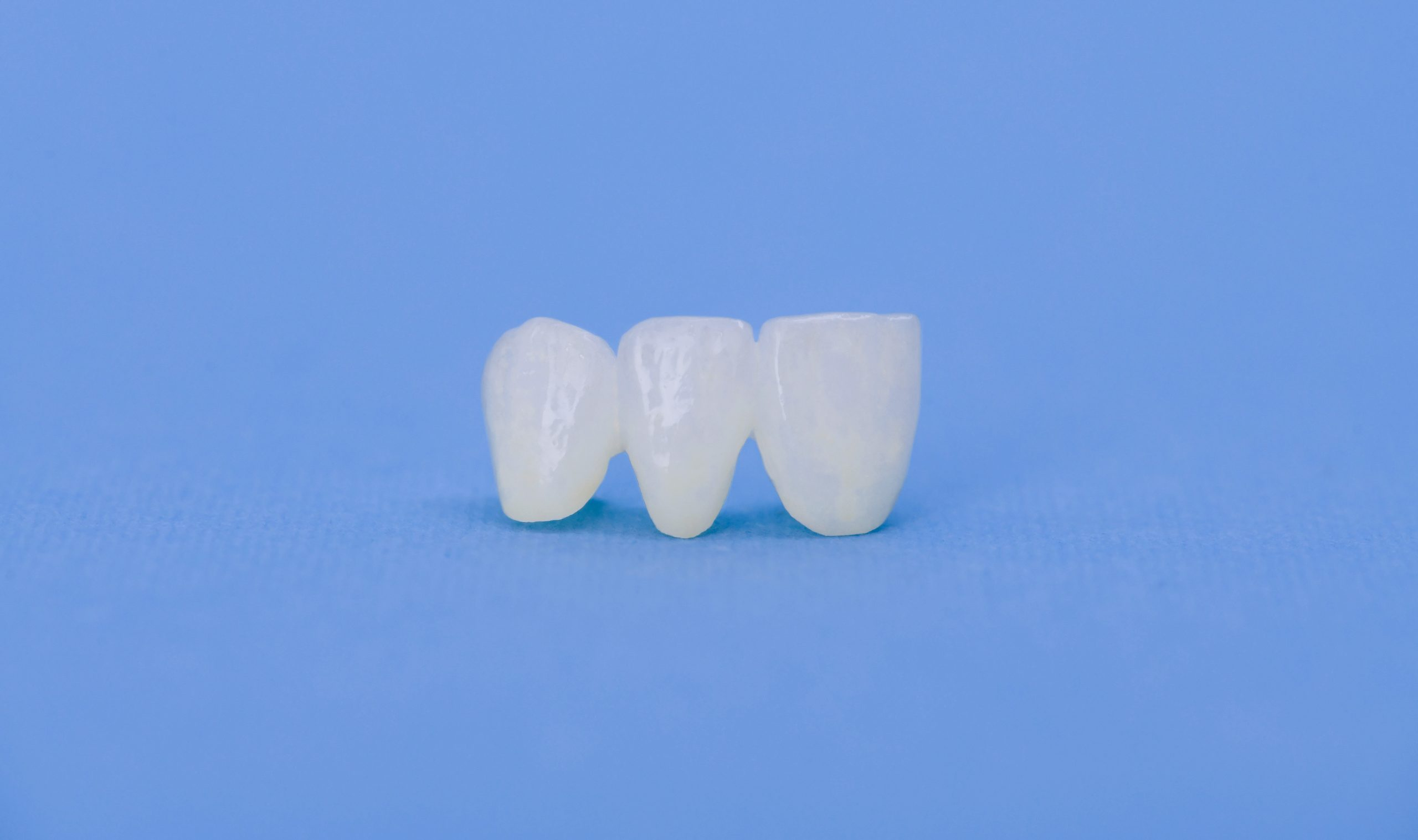 Metal free ceramic dental crowns isolated on a blue background