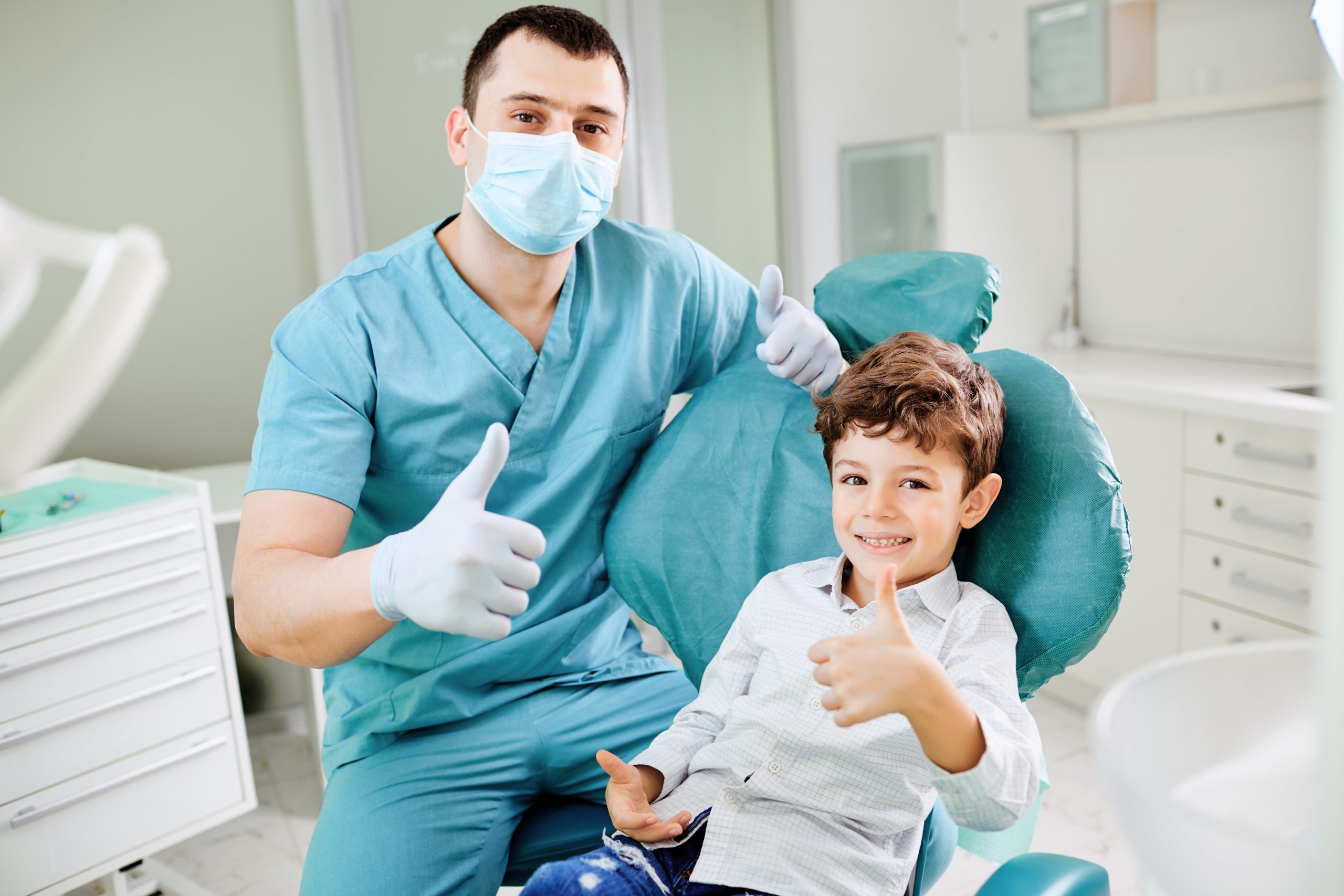 Happy dentist and child raised their thumb up at the dental clinic.
