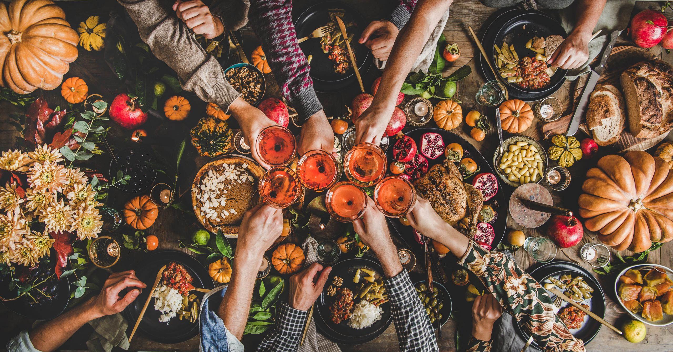 Family celebrating Thanksgiving day. Flat-lay of feasting peoples hands clinking glasses with rose wine over Friendsgiving table with traditional Fall food, roasted turkey, pumpkin pie, top view