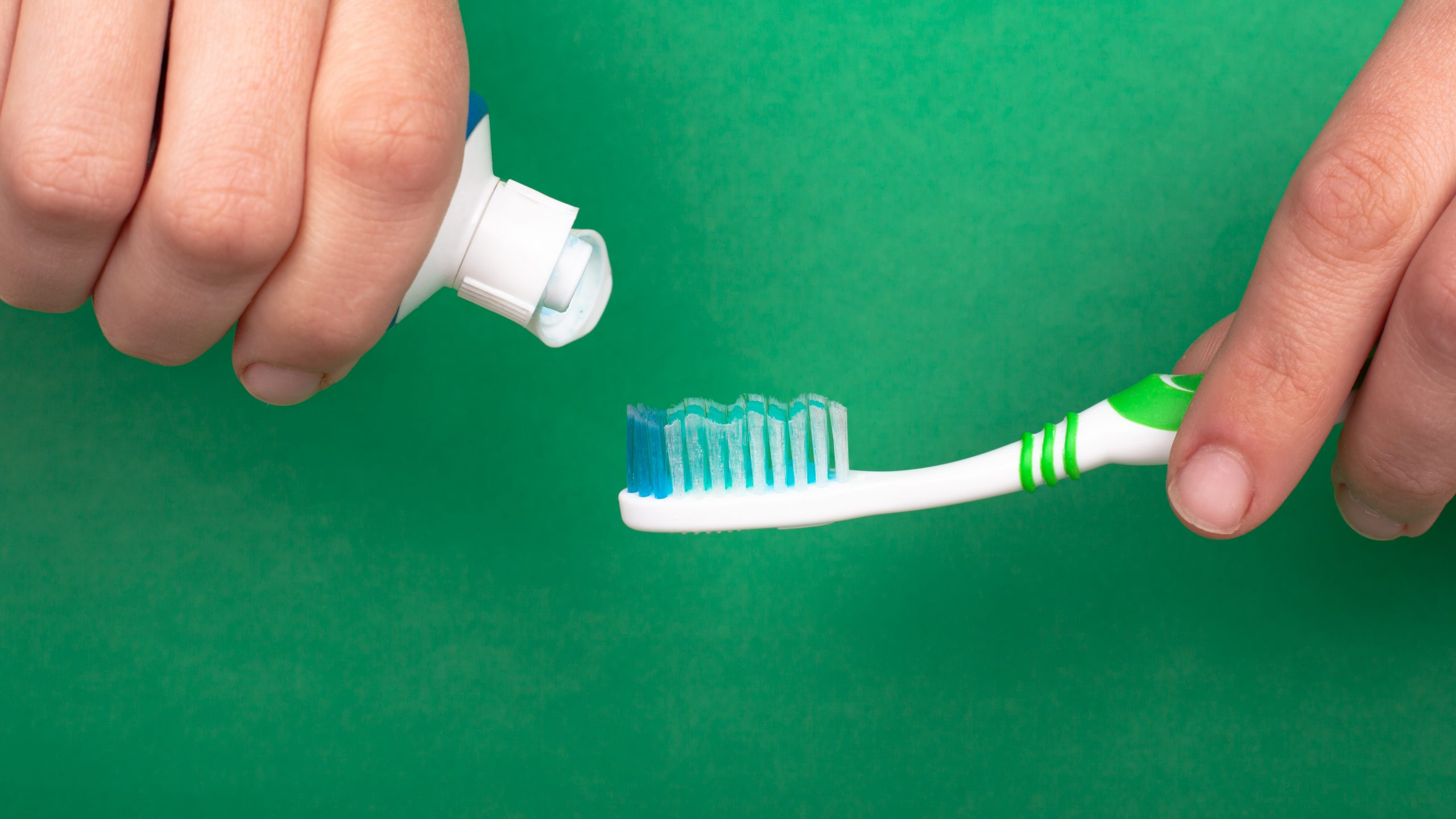 hand squeezes a toothpaste onto a toothbrush on a green background close-up. dental and oral care tooth decay.
