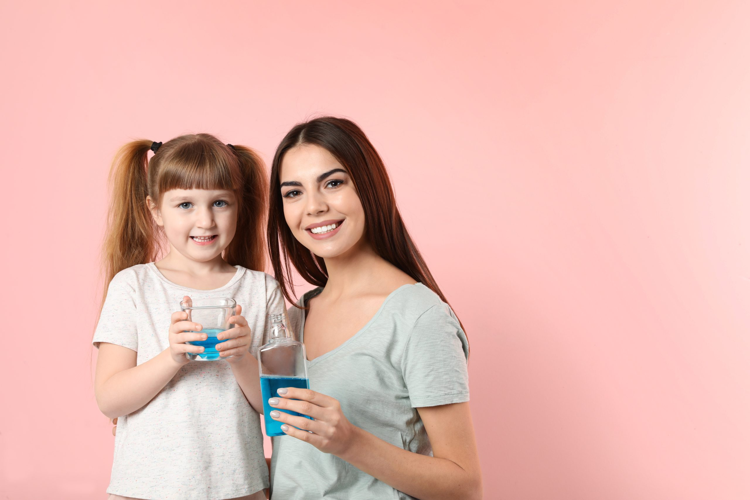 Little girl and her mother with mouthwash on color background, space for text. Teeth and oral care