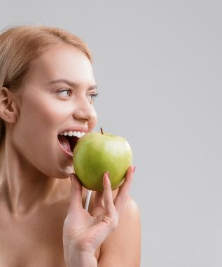Happy young woman is biting green apple with appetite. She is standing and looking aside with joy. Isolated and copy space in right side