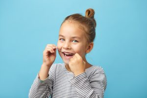 Isolated portrait - dental flush, caucasian child girl using flossing teeth and smiling
