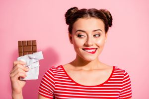 Close-up portrait of nice cute charming attractive winsome glamorous cheerful girl wearing striped t-shirt holding in hands looking favorite dessert life lifestyle advert isolated on pink background.